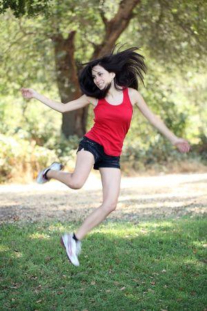latina teen: Young latina teen girl jumping outdoors motion blur