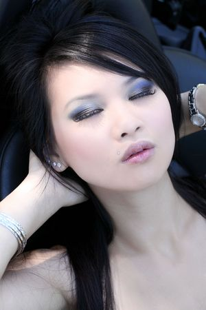 Young Oriental woman reclining with eyes closed portrait 版權商用圖片