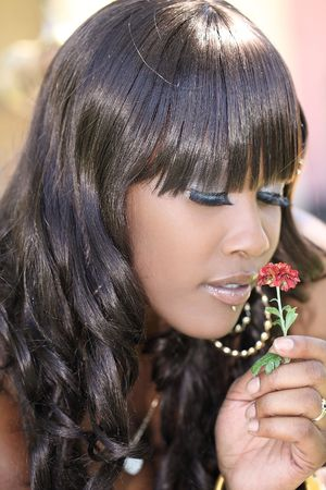 Young African American woman holding flower with eyes closed 版權商用圖片