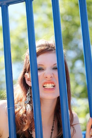 Young teen girl snarling through playground blue bars