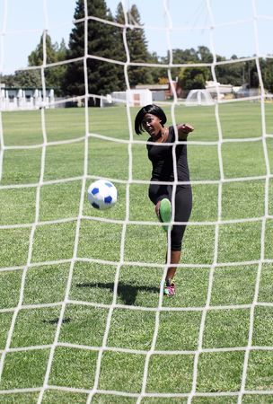 Young African American woman kicking soccer ball goal photo