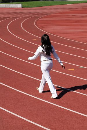Young African American woman walking for exercise on outdoor track