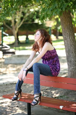 Young teen woman sitting in jeans and purple top