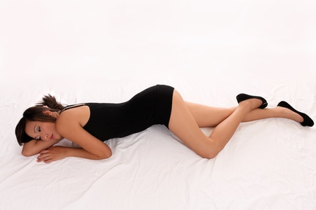 Young Asian woman reclining on floor in black dress Stock Photo