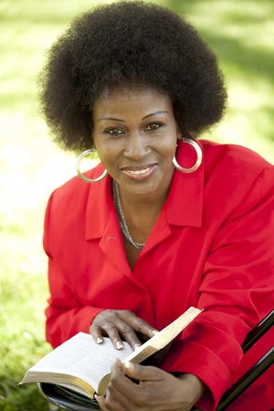 African American Woman reading Bible red top outdoors