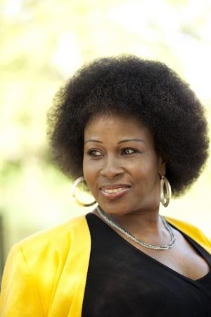 African American Woman outdoor portrait black dress yellow jacket Archivio Fotografico