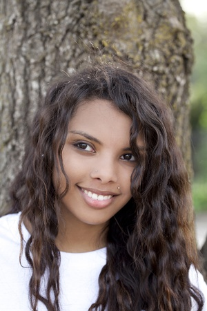 latina teen: Young attractive latina teen girl against oak tree Stock Photo
