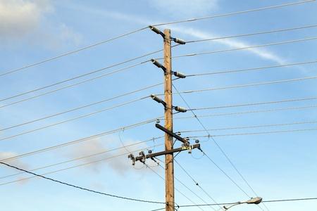 power pole against blue sky high voltage lines horizontal