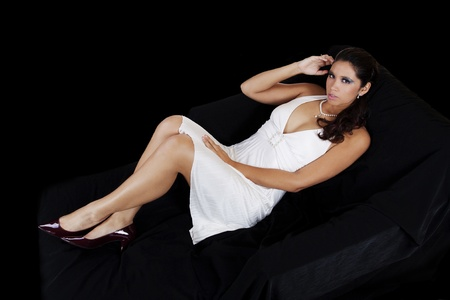 Young latina woman reclining on black cloth over chair