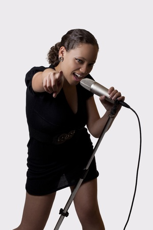 Young black woman singing into mic pointing  Stock fotó