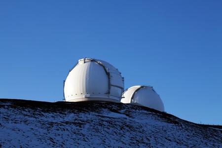 two white buildings housing telescopes on mountain top