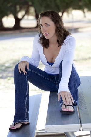 Young woman sitting on picnic table jeans and shirt photo