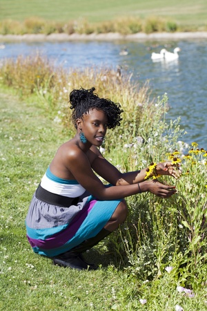 Young black woman outdoors squatting at park photo