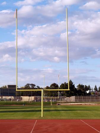 goalpost: Yellow goal posts empty football field daytime white clouds