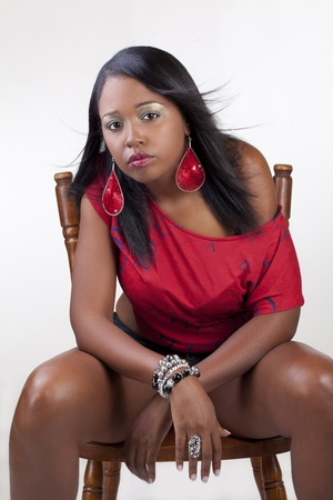 Young African American woman sitting on chair red top