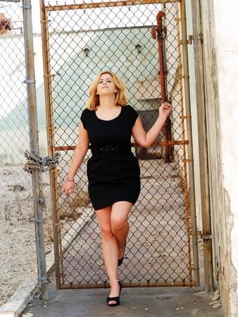 Jonge Kaukasische vrouw leunend tegen hek zwarte jurk Stockfoto
