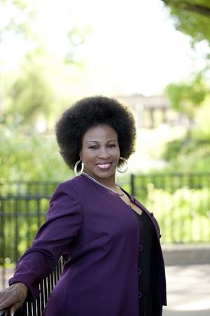 black: Middle-Aged Black woman outdoor portrait purple jacket black dress Stock Photo