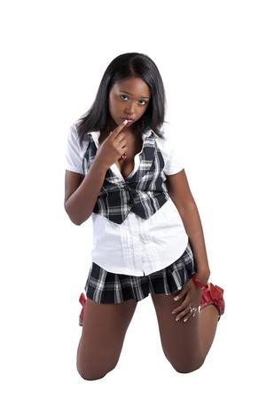 donna in ginocchio: Giovane donna afro-americana in ginocchio con un dito sulle labbra