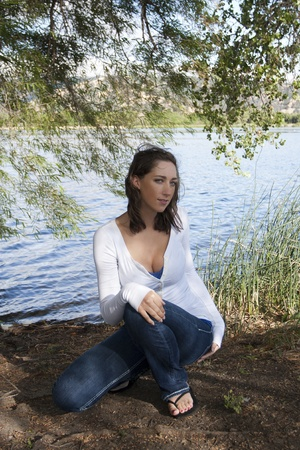 Young woman on lake edge jeans and white top photo