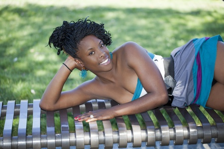 recline: Young African American woman reclining on bench outdoors