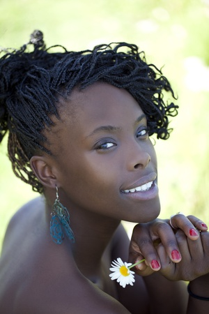 Young African American woman outdoor portrait flower braids