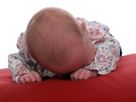 Young caucasian baby on stomach red pillow