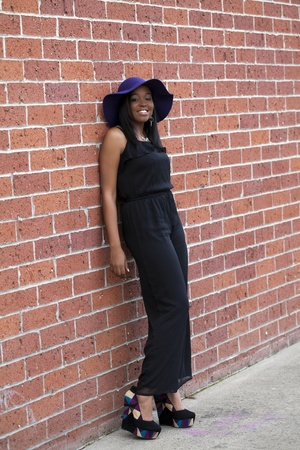 Young Black woman standing against red brick wall photo