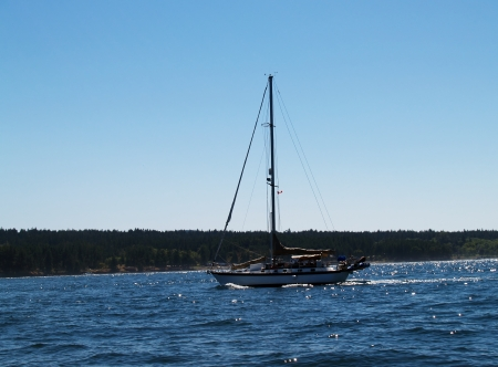 furled: Sailboat with Sails Furled Moving Under Power Stock Photo