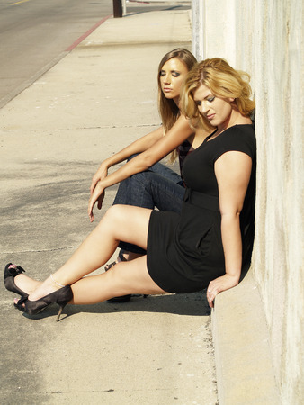 Skinny en Plump Woman Sitting Sidewalk Sunny Day Stockfoto