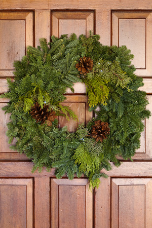 Green Christmas Wreath Hanging On Wooden Door