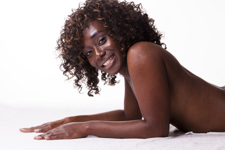 Black Woman Reclining Topless Breast Covered Smiling photo