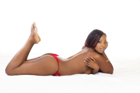 nude black women: Black Woman On Stomach Topless Red Bikini Stock Photo