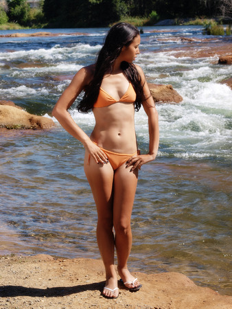 skinny woman: Skinny Woman Orange Bikini Standing At River