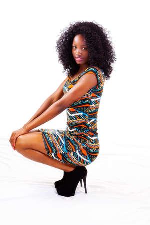 girl squatting: Attractive Black Teen Girl In Dress Squatting