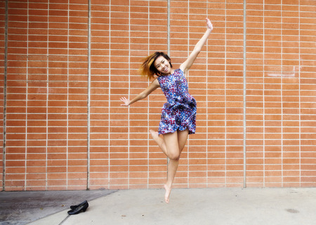 asian american: Attractive Asian American Woman Jumping In Dress Stock Photo