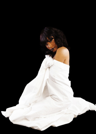white sheet: Black Woman Sitting On Floor Wrapped In White Sheet Stock Photo