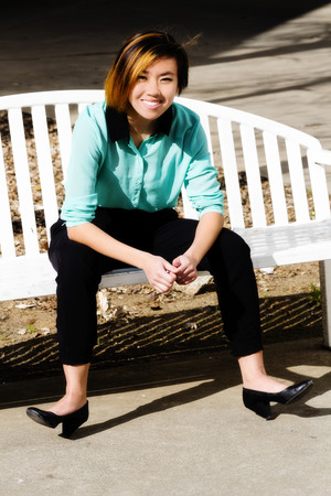 asian american: Smiling Asian American Woman Outdoors On Bench Stock Photo
