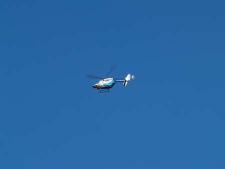 skids: Small Helicopter In Flight Against Blue Sky