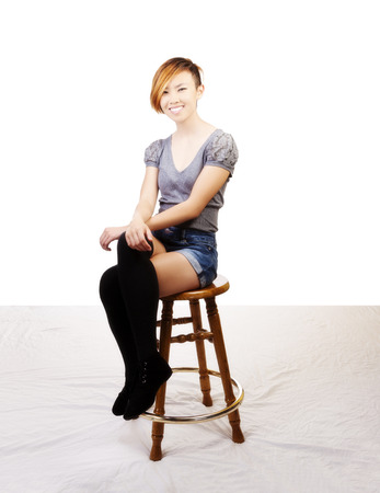 Smiling Asian American Woman Sitting On Stool Stock Photo