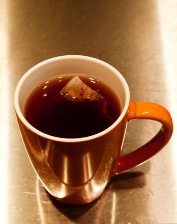 stove top: Tea Bag Steeping In Orange Cup On Metal Stove Top