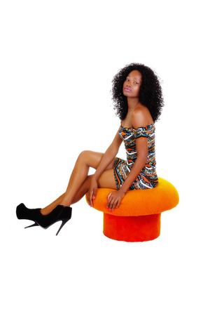 sitting pretty: Attractive Black Woman Sitting In Patterned Dress