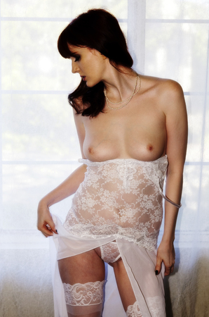 red breast: Topless Woman Standing Before Window White Lingerie Stock Photo