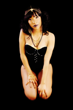 Attractive Black Woman Kneeling In Leotard With Dark Background Banque d'images