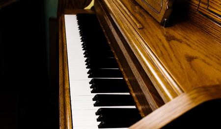 upright piano: Tight Shot Of Upright Piano Keyboard And Surrounding Wood