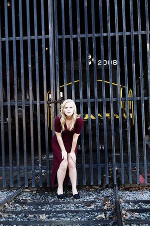 Aantrekkelijke blonde vrouw Rode Kleding Openlucht Op Sporen van de spoorweg Stockfoto