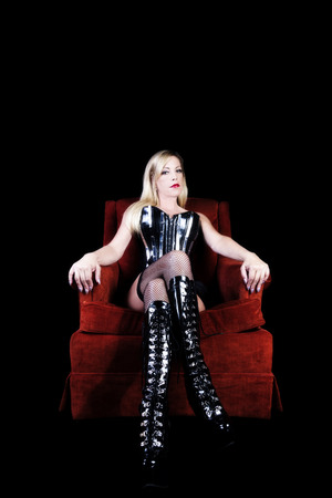 Older Blond Woman In Black Corset Fishnet Stockings And Boots Sitting On Red Chair 스톡 콘텐츠