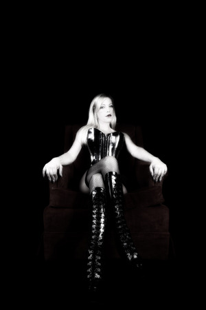 Older Blond Woman In Black Corset Fishnet Stockings And Boots Sitting On Red Chair Фото со стока
