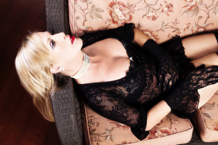 recline: Middle Aged Caucasian Woman Reclining On Chair In Black Lace Lingerie Stock Photo