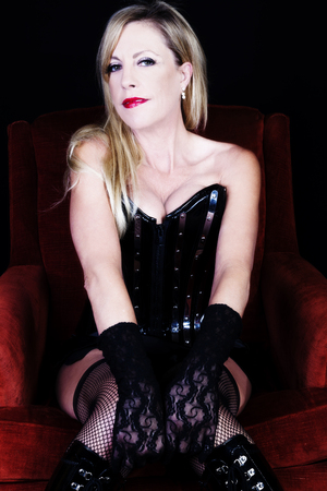 red corset: Older Caucasian Blond Woman Sitting On Red Chair In Black Corset Fishnet Stockings Lace Gloves Showing Cleavage Stock Photo