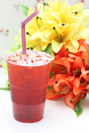 Glass of ice fruit tea with fabric flowers